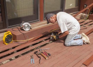 Senior repairing wood deck