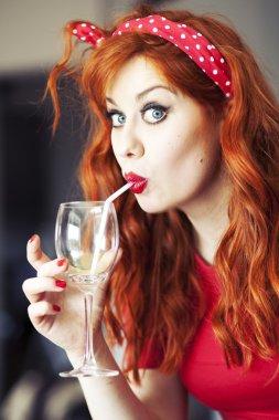 Funny girl drinking wine using straw.