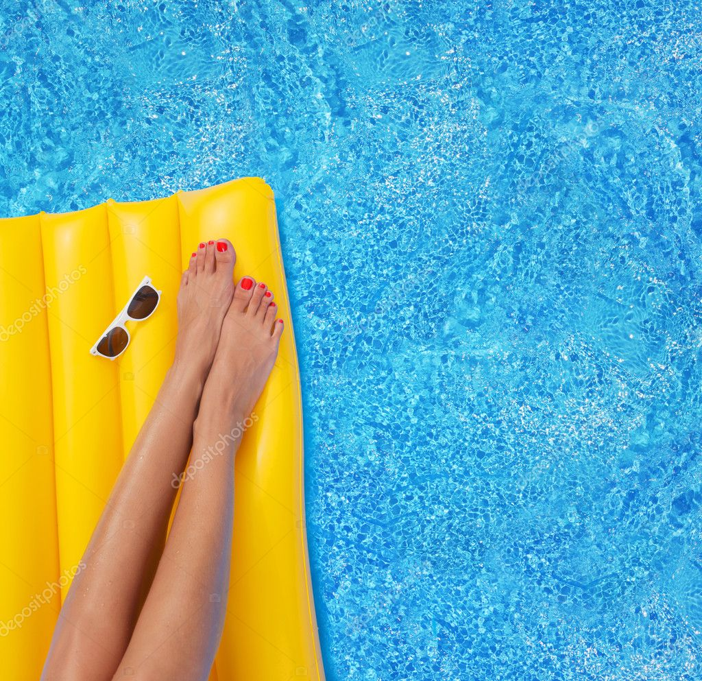 Woman relaxing in a pool - feet close up