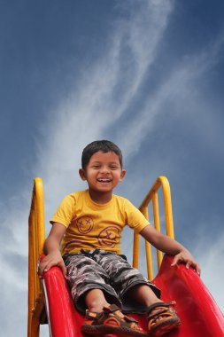 Happy smiling and handsome indian kid having fun playing in slid