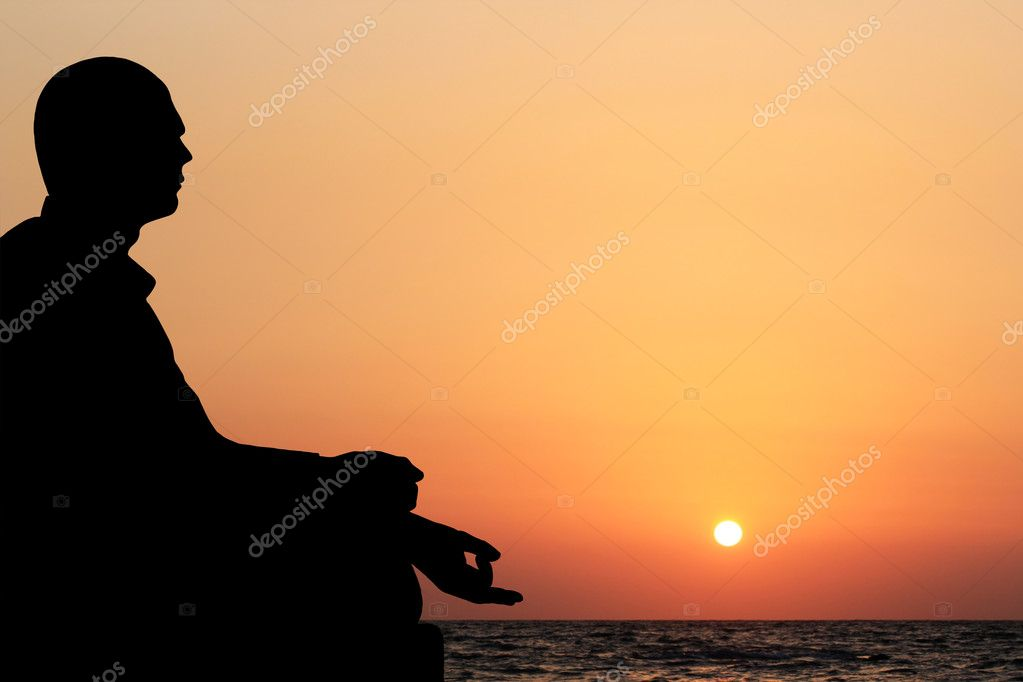 A young man sitting in lotus position and meditating on a beach