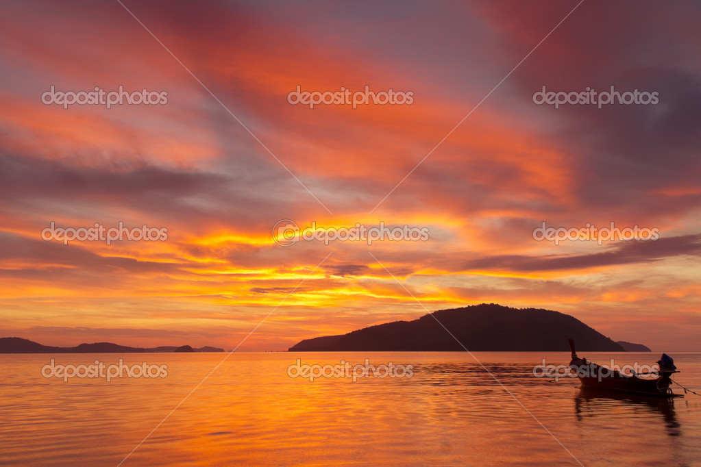 Vivid color sunrise in Phuket, Thailand, with far island and a fishing boat silhouette