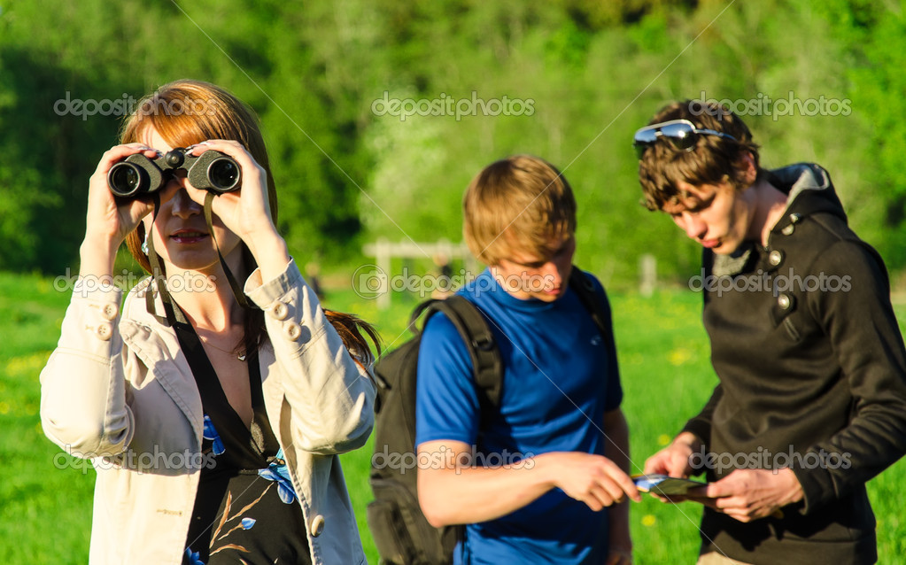 Three friends traveling. Girl looking through binoculars