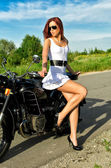 Sexy young woman posing near vintage motorbike