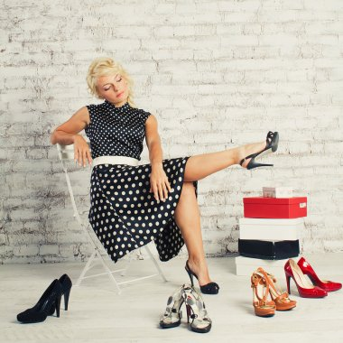 Slopaholic blonde girl in dress sitting with shoes and boxes
