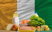 Basic food groceries in front of ivory coast national flag