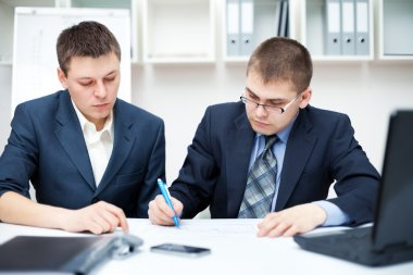 Two young business sitting at desk working in team togeth