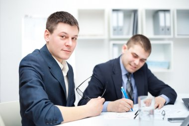 Two young businessmen signing contracts in office