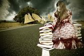 Fotografia ragazza con i libri a tempo di volo sulla strada