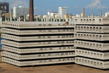 Pallets of new concrete blocks under sunlight against blue sky