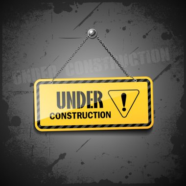 Under construction sign hanging with chain on grunge background