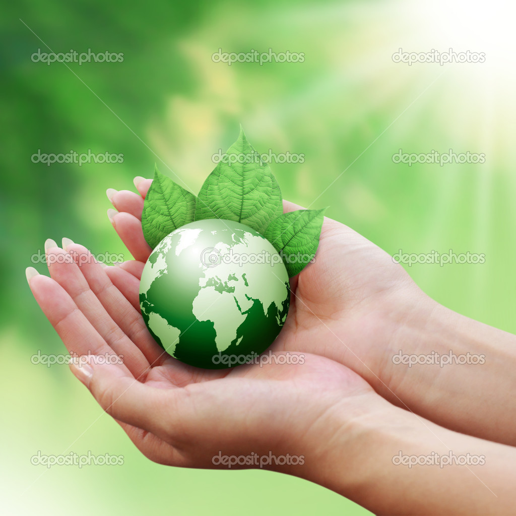 Human hands holding green globe with a leaf