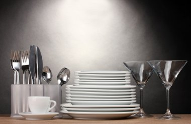 Clean plates, glasses, cup and cutlery on wooden table on grey background