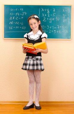 Beautiful little girl in school uniform with books in class room