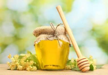 Jar with linden honey and flowers on wooden table on green background