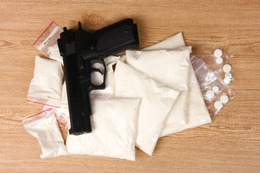 Cocaine and marihuana in packages and handgun on wooden background