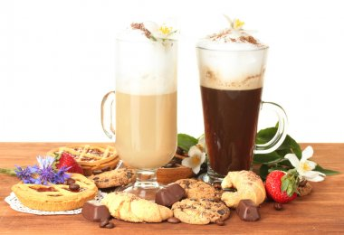 Glasses of coffee cocktail on wooden table with sweet and flowers on white background