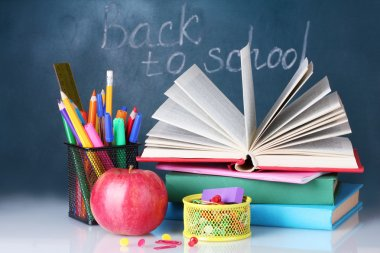 Composition of books, stationery and an apple on the teacher's desk in the background of the blackboard. Back to school.