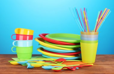 Bright plastic disposable tableware on wooden table on colorful background