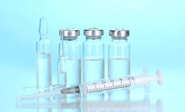 Syringe and medical ampoules on blue background
