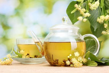 Teapot and cup with linden tea and flowers on wooden table in garden