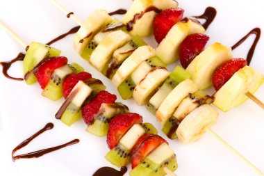 Mixed fruits and berries on skewers with chocolate close-up