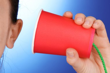 Human ear and paper cup near it close-up on blue background