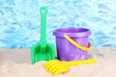 Children's beach toys on sand on water background