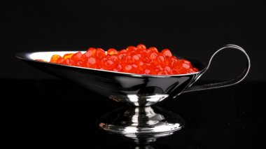 Red caviar in silver bowl isolated on black