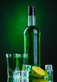 Fotografie Flasche und Gläser Absinth mit Limette und Eis auf grünem Hintergrund