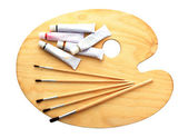 Wooden art palette, tubes with paint and brushes isolated on white