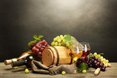 Photo Barrel, bottles and glasses of wine and ripe grapes on wooden table on grey background
