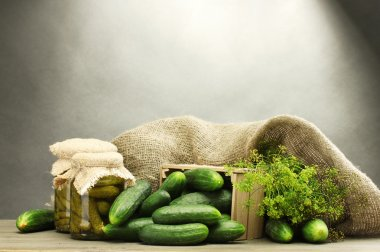 Fresh cucumbers in wooden box, pickles and dill, on grey background