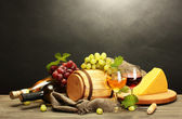 Barrel, bottles and glasses of wine, cheese and ripe grapes on wooden table on grey background
