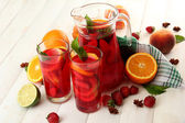 Sangria in jar and glasses with fruits, on white wooden table