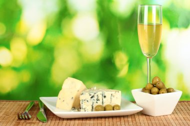 Composition of blue cheese, glass of wine and olives on bright green background close-up