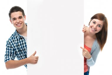 Smiling teenagers holding at a blank board