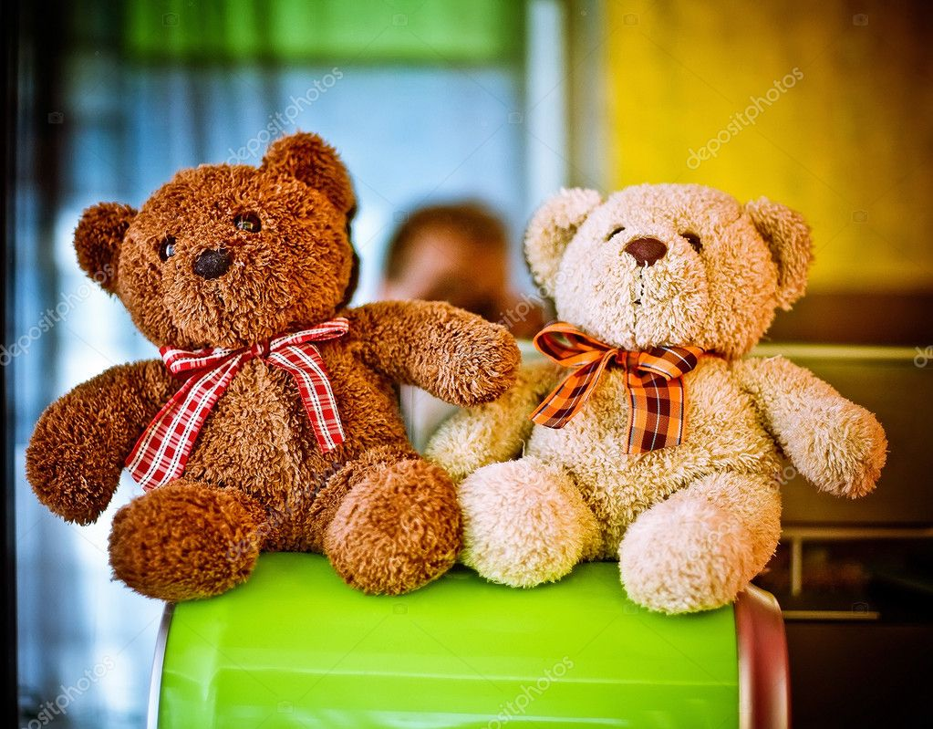 Two stuffed bears seat in a kid room