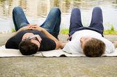 Two guys relaxing alongside a river