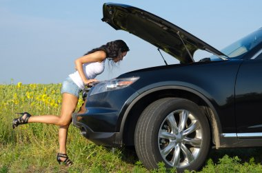 Woman in sexy shorts checking engine