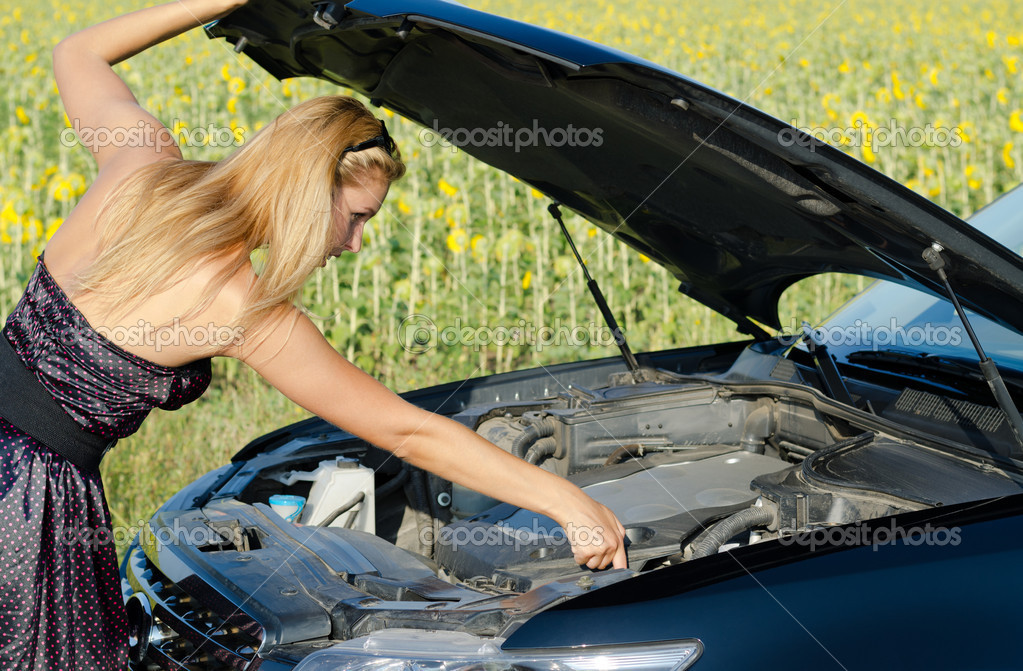 Woman checking the engine oil