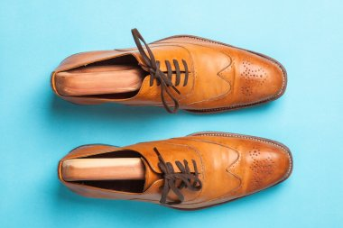 A pair of tan fashionable mens brogue shoes on a bright blue background