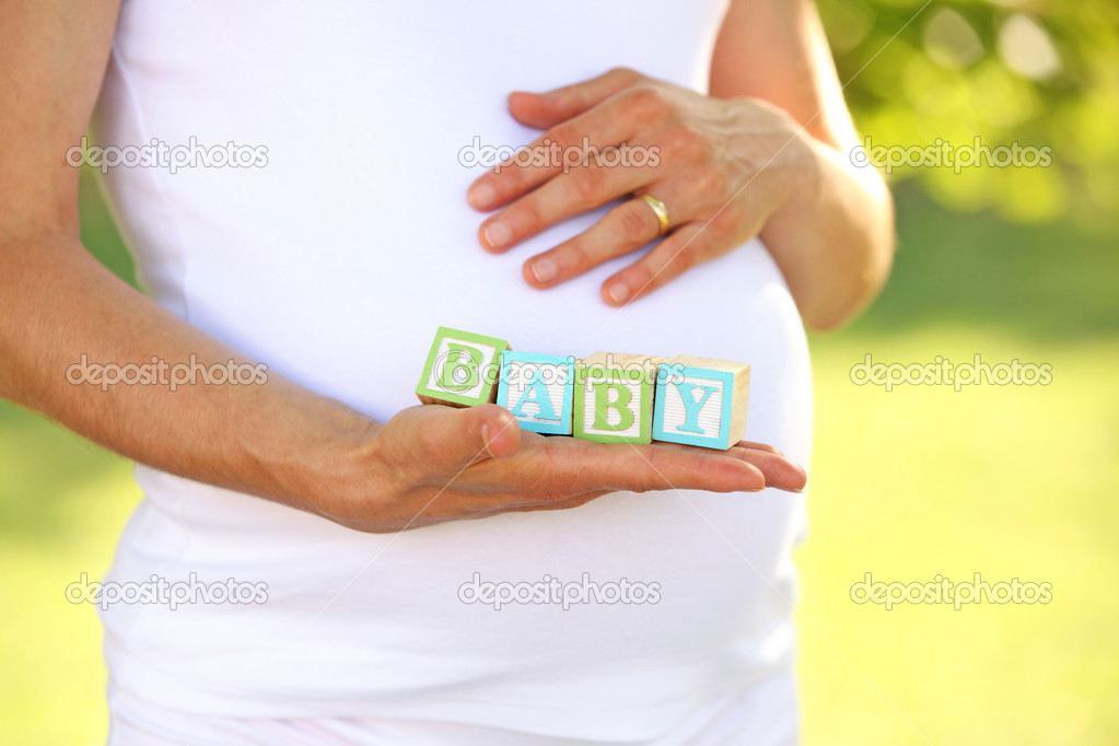 Pregnant woman holding word baby