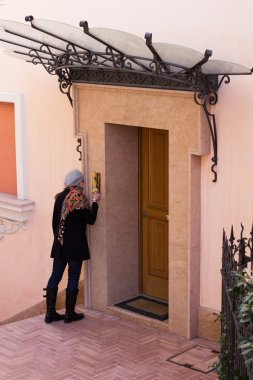 Woman Ringing The Entrance Door To A Flat