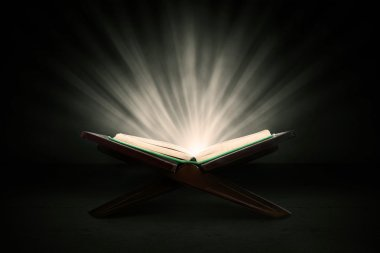 Muslim holy book of koran shot in studio on dark background, with shiny rays stock vector