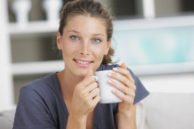 Close-up of a young woman smiling and drinking coffee