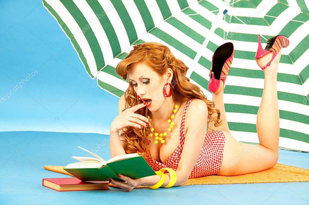 df023c016d0ea Beautiful sexy girl pin up in a pink bikini reads book on the beach under  sun umbrella– stock image
