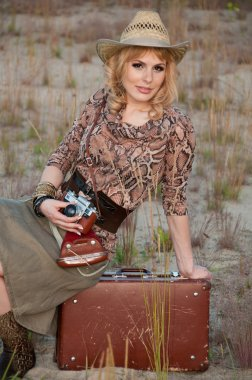 A girl travels in a cowboy hat, with a camera and a suitcase in