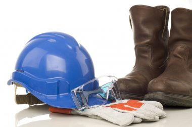 A set of protective equipment such as hard hat, safety glass, semi leather gloves and safety shoes isolated with white background stock vector