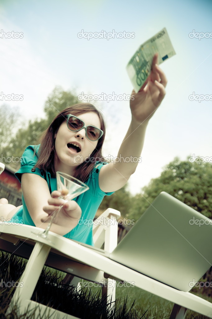 Woman lying on the lounge and holding a wineglass with a banknot